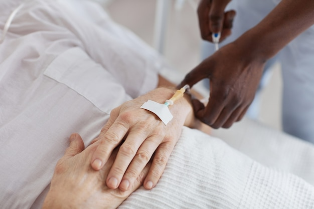 Крупным планом афро-американский медсестра устанавливает капельницу, ухаживая за пожилым мужчиной в больнице, копия пространства