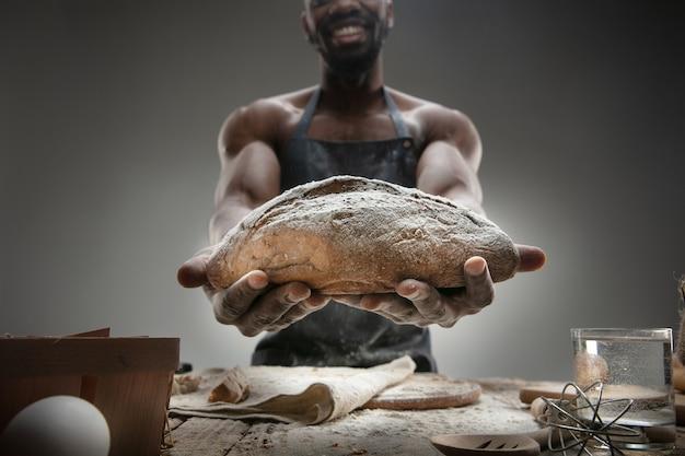 Крупным планом афро-американский мужчина готовит свежие хлопья, хлеб, отруби на деревянном столе. вкусная еда, питание, крафтовый продукт. безглютеновая пища, здоровый образ жизни, экологически чистое и безопасное производство. ручной работы.