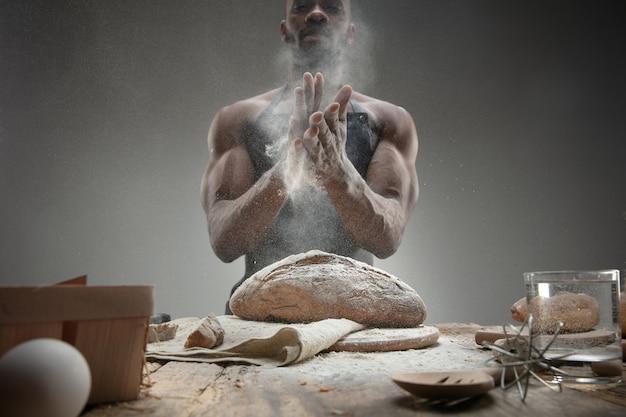 アフリカ系アメリカ人の男性のクローズアップは、木製のテーブルで新鮮なシリアル、パン、ふすまを調理します。おいしい食事、栄養、工芸品。グルテンフリー食品、健康的なライフスタイル、オーガニックで安全な製造。手作り。