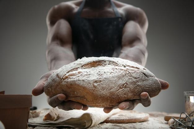 アフリカ系アメリカ人の男性のクローズアップは、木製のテーブルで新鮮なシリアル、パン、ふすまを調理します。おいしい食事、栄養、工芸品