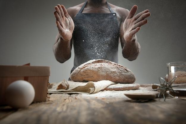 Афро-американский мужчина готовит свежие хлопья, хлеб, отруби на деревянном столе