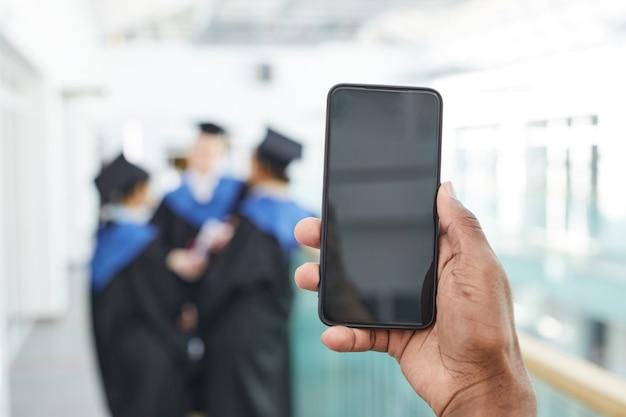 Крупным планом афро-американского мужчины, держащего смартфон с пустым экраном перед камерой с группой выпускников колледжа в фоновом режиме, копией пространства