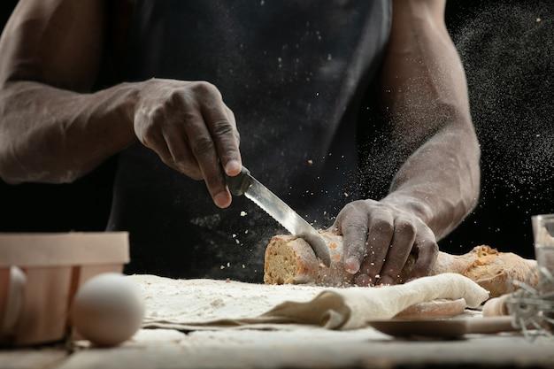 アフリカ系アメリカ人の男のクローズアップは、包丁で焼きたてのパンをスライスします