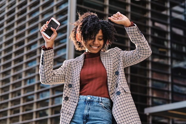 金融都市地区の屋外でヘッドフォンと携帯電話で音楽を聴きながら踊って楽しんでいるアフリカ系アメリカ人女性のクローズアップ。