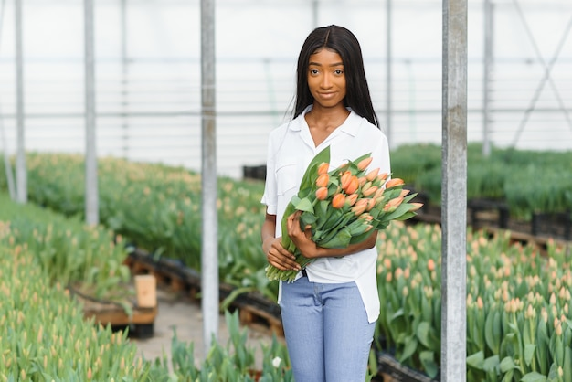 Крупным планом афро-американской женщины, держащей цветы в теплице