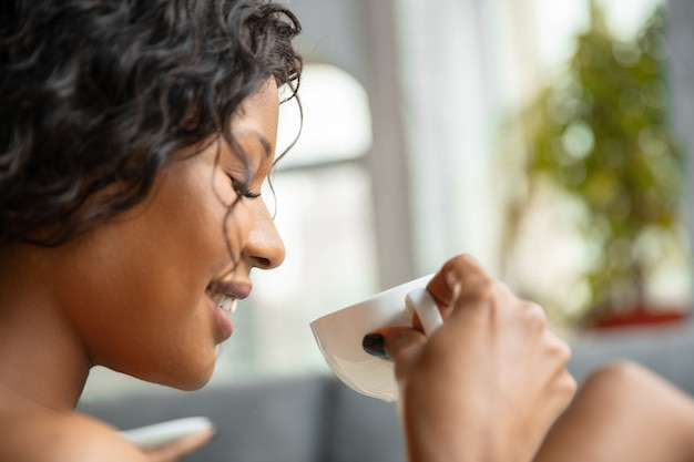 自宅で彼女の毎日の美容ルーチンをしているタオルでアフリカ系アメリカ人の女性のクローズアップ。ソファに座って、満足そうに見え、コーヒーを飲み、リラックスします。美容、セルフケア、化粧品、若者の概念。
