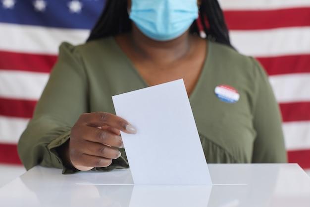 투표 용지 상자에 투표 게시판을 넣고 선거일에 미국 국기에 서있는 동안 마스크를 착용하는 아프리카 계 미국인 여자의 닫습니다, 복사 공간