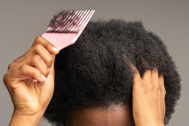 스튜디오 회색 벽에 격리된 곱슬머리를 빗질하는 아프리카 여성 클로즈업