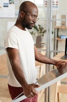Крупный план африканского человека, изучающего жидкокристаллическую панель в его руках во время работы в офисе