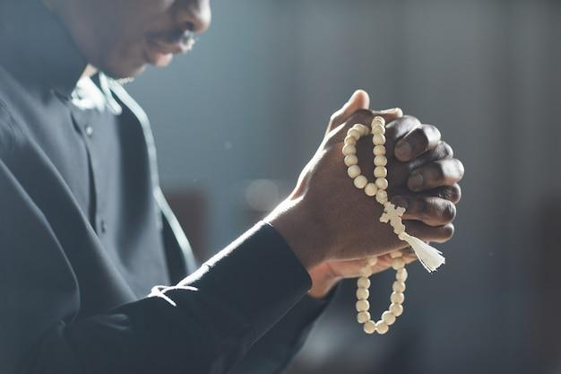 Крупный план африканского мужчины, держащего четки в руках и молящегося в церкви
