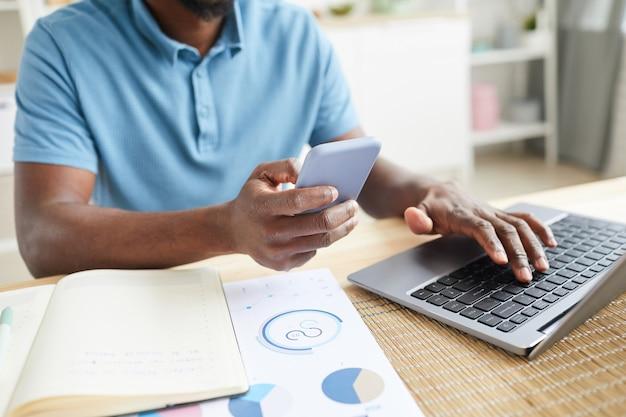 書類を持ってテーブルに座って、自宅で仕事をしているラップトップに携帯電話を接続しているアフリカ人男性のクローズアップ