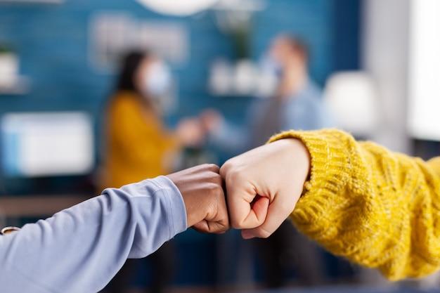 Крупным планом - африканская женщина и друг, ударившись кулаком, приветствуют друг друга в домашней гостиной, сохраняя социальное дистанцирование в качестве меры предосторожности во время глобальной пандемии коронавируса. Premium Фотографии