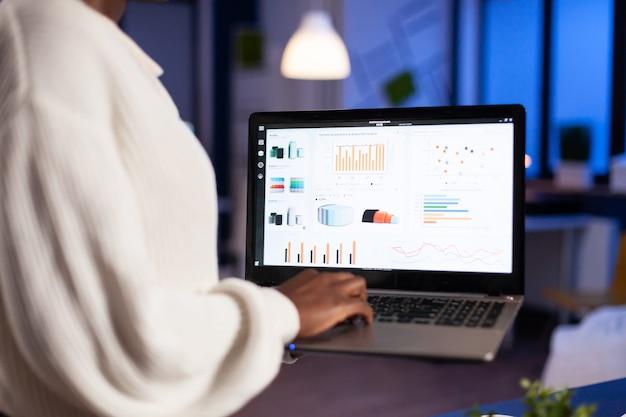 노트북을 사용하여 사무실에서 밤늦게 야근을 하는 아프리카 여성 클로즈업