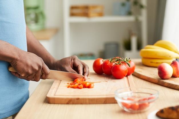 キッチンのまな板でトマトを切るアフリカの若い男のクローズアップ