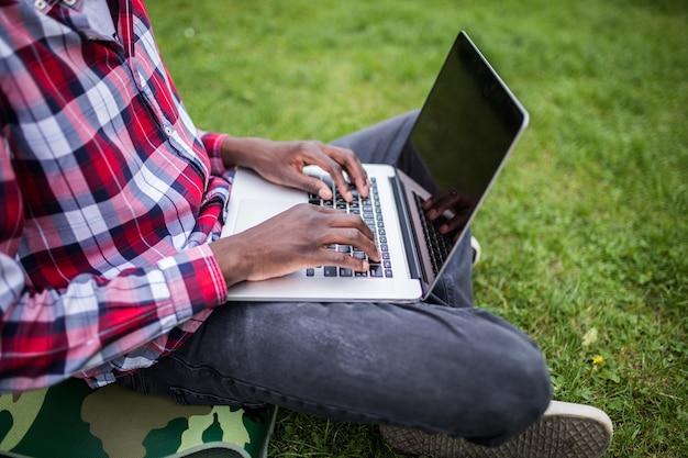 緑の芝生の上のラップトップに入力するアフロアメリカンの手のクローズアップ