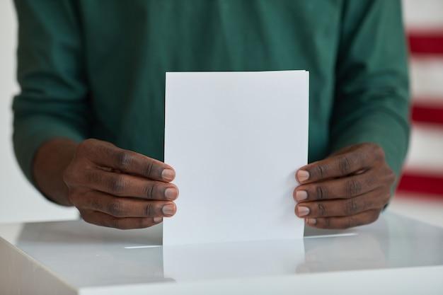 投票箱の近くに立って投票用紙を保持しているアフリカ系アメリカ人の有権者のクローズアップ