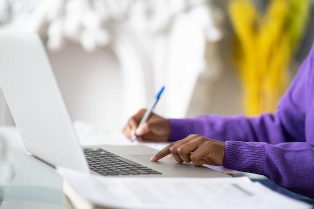 アフリカ系アメリカ人の女性従業員またはラップトップを使用している学生のクローズアップ、指でタッチパッドに触れ、ペンでメモを作成します。選択的なソフトフォーカス。