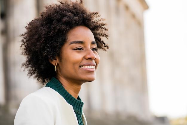 通りで屋外に立っている間笑顔のアフロビジネス女性のクローズアップ。ビジネスと都市のコンセプト。