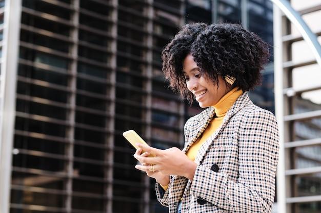 金融都市地区で屋外で働く途中で彼女の携帯電話をチェックしているアフロ実業家のクローズアップ。
