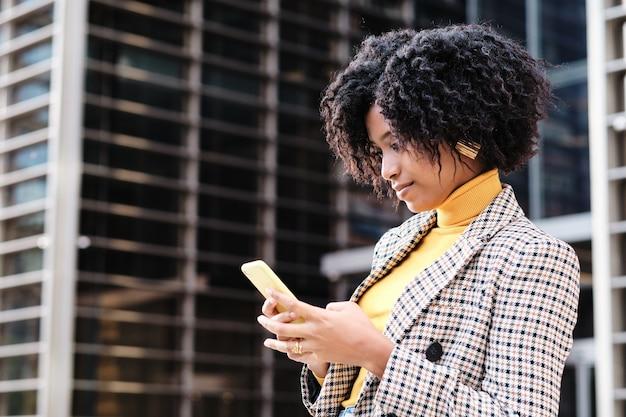 金融都市地区の屋外に立っているときに彼女の電話でメッセージを送信するアフロ実業家のクローズアップ。