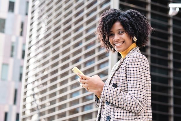 彼女の携帯電話を使用して、金融都市地区で屋外を歩いている間笑顔でアフロ実業家のクローズアップ。