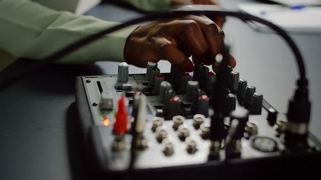 인플 루 언서가 프로 장비로 소셜 미디어 콘텐츠를 기록하는 동안 사운드 조정을하는 아프리카 동영상 블로거의 클로즈업