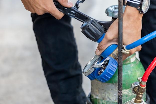 Крупный план работника по ремонту кондиционеров, устанавливающего манометр на топливных газах и кислородном баллоне для сварки или резки металлов, сварки кислородом и резки кислородом топлива
