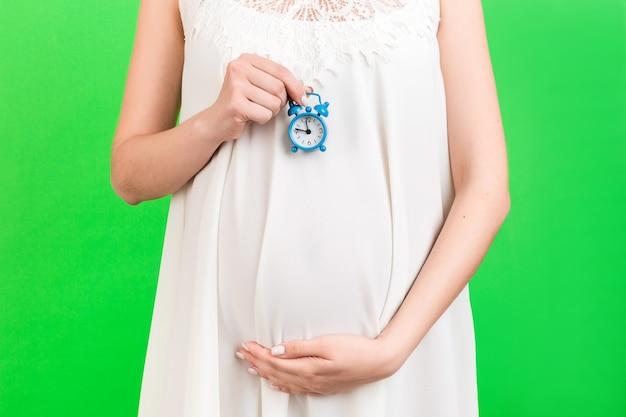 녹색 배경에서 흰색 드레스에 임신 한 여자의 배꼽에 대한 알람 시계 닫습니다