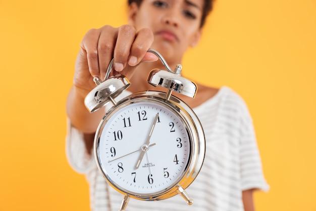 分離された女性の手で目覚まし時計のクローズアップ