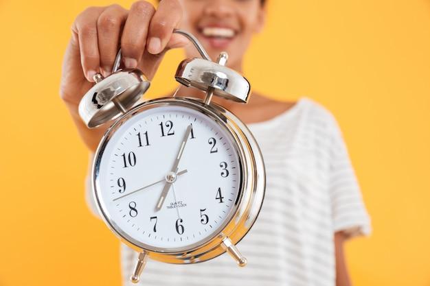Крупным планом будильник в руке женщины изолированы