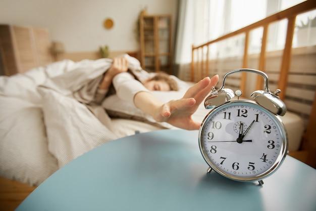 Крупный план будильника на столе с женщиной, выключающей его утром в спальне