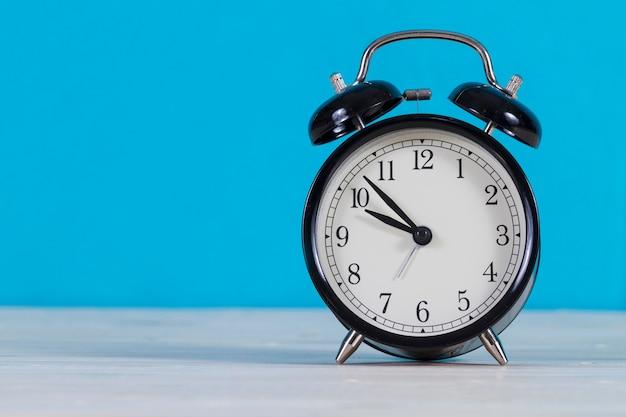 青色の背景色の目覚まし時計のクローズアップ