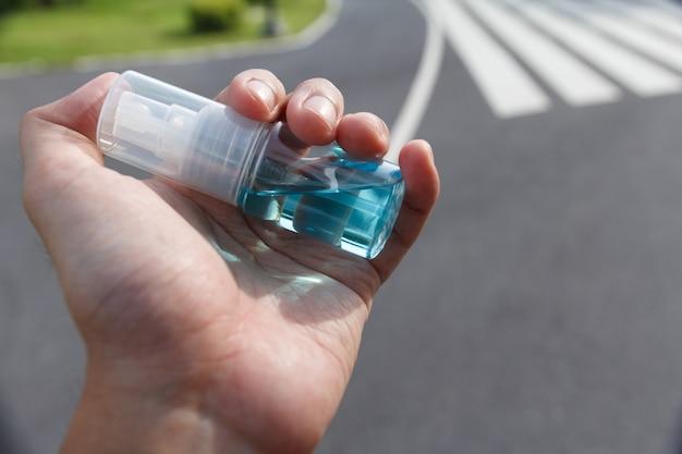 コロナウイルスを保護するために手をきれいにするためにアルコールのクローズアップ。 covid19を保護するために保護マスクとアルコールを使用するキャンペーン