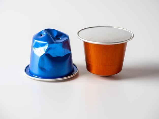 白い背景の上のコーヒーとは異なる色のアルミニウムカプセルのクローズアップ。カプセルの1つが使用されます。原材料の再利用のコンセプト