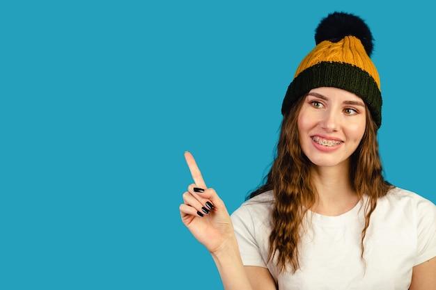 검지 손가락으로 방향을 보여주는 모자에 중괄호와 함께 놀라운 웃는 갈색 머리의 클로즈업.