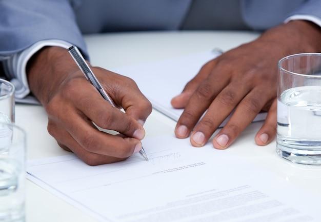 契約に署名する野心的なビジネスマンのクローズアップ
