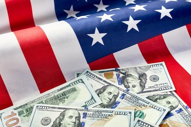 アメリカの国旗とドルの現金のクローズアップ。ドル紙幣と米国旗の背景。