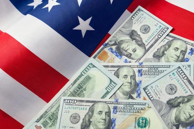 アメリカの国旗とドルの現金のクローズアップ。ドル紙幣と米国旗。