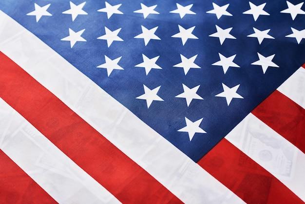 多くの米ドル紙幣の上にアメリカ国旗のクローズアップ。財務の概念