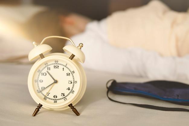 目覚まし時計と睡眠マスクのクローズアップ、女の子は背を向けて眠ります。彼女は長い間眠り、朝遅く、太陽が輝いています。
