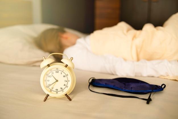 目覚まし時計と睡眠マスクのクローズアップ、女の子は背を向けて眠ります。朝遅く、長い間眠ります。
