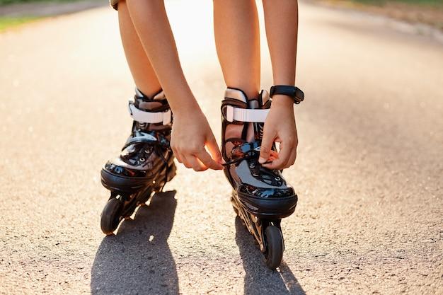 スケートをする前にローラーブレードに靴ひもを固定している匿名の子供の手のクローズアップ、晴れた夏の日の道路上の未知の子供、ローラーブレード、アクティブなライフスタイル。