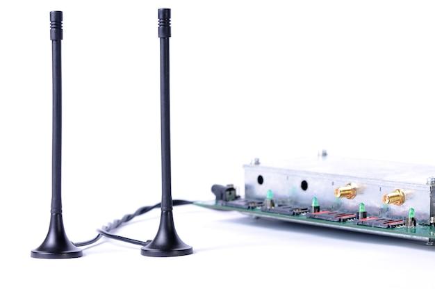 전자 회로 기판과 흰 벽에 서있는 전자 장치로 이어지는 전선이있는 안테나의 클로즈업. 간첩 및 군사 장비의 개념. 광고 공간
