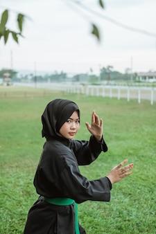 공원 배경에 측면 자세와 pencak silat 유니폼을 입고 아시아 가려져 여자의 닫습니다