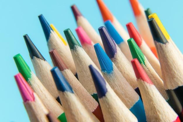 Закройте ассортимент цветных карандашей на синем фоне.