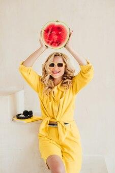그녀의 손에 수분이 많은 수박과 함께 노란색 옷과 여름 선글라스에 매력적인 웃는 세련된 여자의 클로즈업. 행복한 여름, 휴가, 영감. 부드러운 선택적 초점입니다.