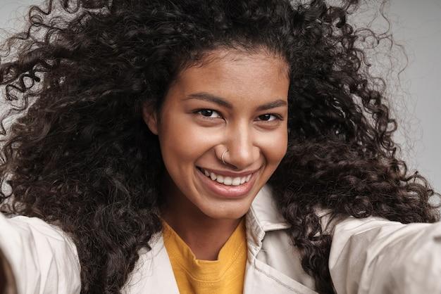 Крупным планом привлекательная улыбающаяся молодая африканская женщина с вьющимися волосами в осеннем пальто