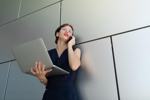 그녀의 손에 노트북과 붉은 입술으로 매력적인 젊은 비즈니스 여자의 근접 사무실 건물의 회색 벽에 기댄 전화로 약속을합니다