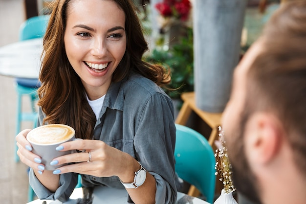 屋外のカフェのテーブルに座って、コーヒーを飲みながら、おしゃべりしながら昼食をとるのが大好きな魅力的な若いカップルのクローズアップ