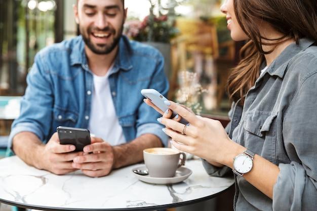 携帯電話を使用して、屋外のカフェのテーブルに座って昼食をとるのが大好きな魅力的な若いカップルのクローズアップ